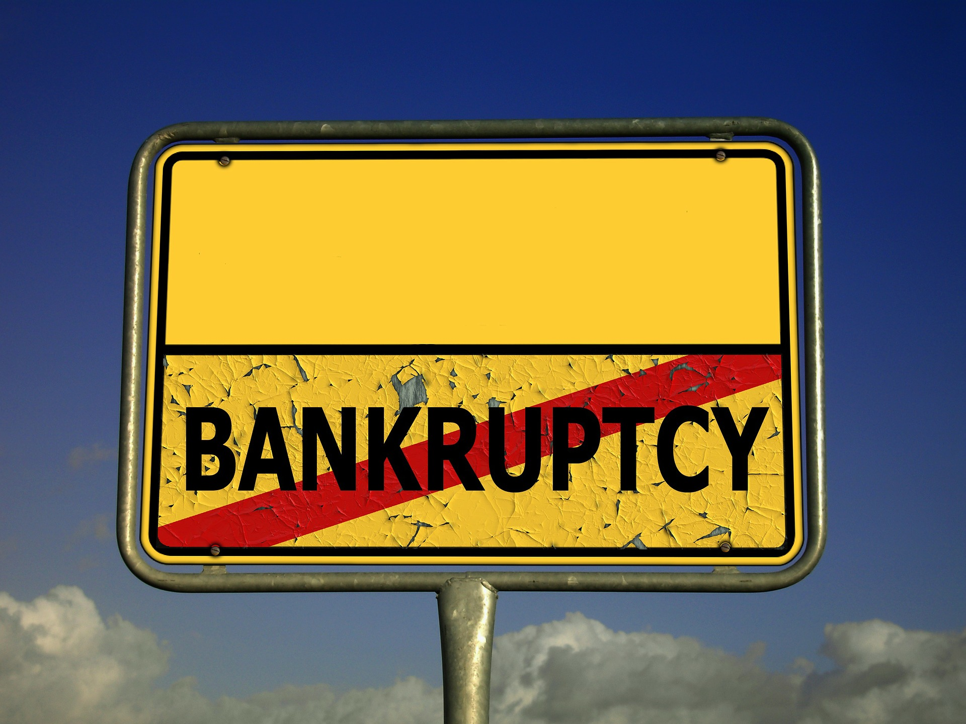 "A yellow road sign with black writing that reads ""bankruptcy"""