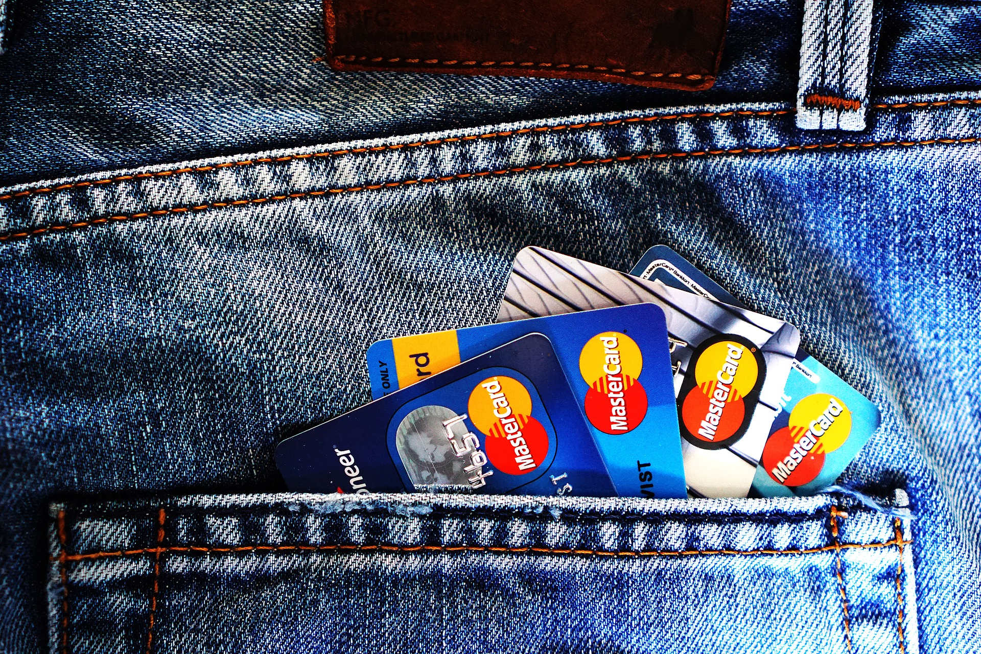 Denim jean pocket holding four credit cards
