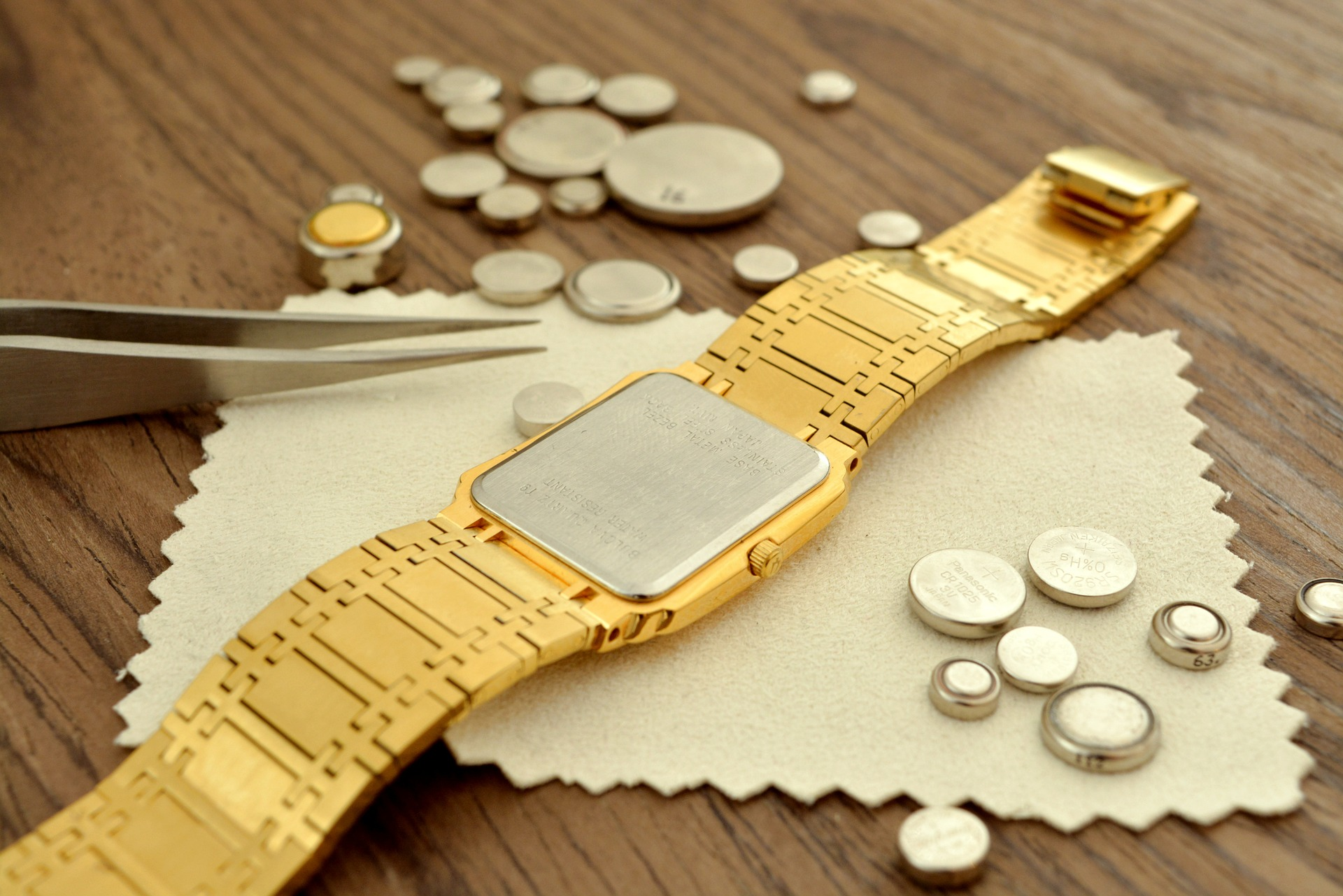 A gold watch on a table with button batteries scattered around the watch