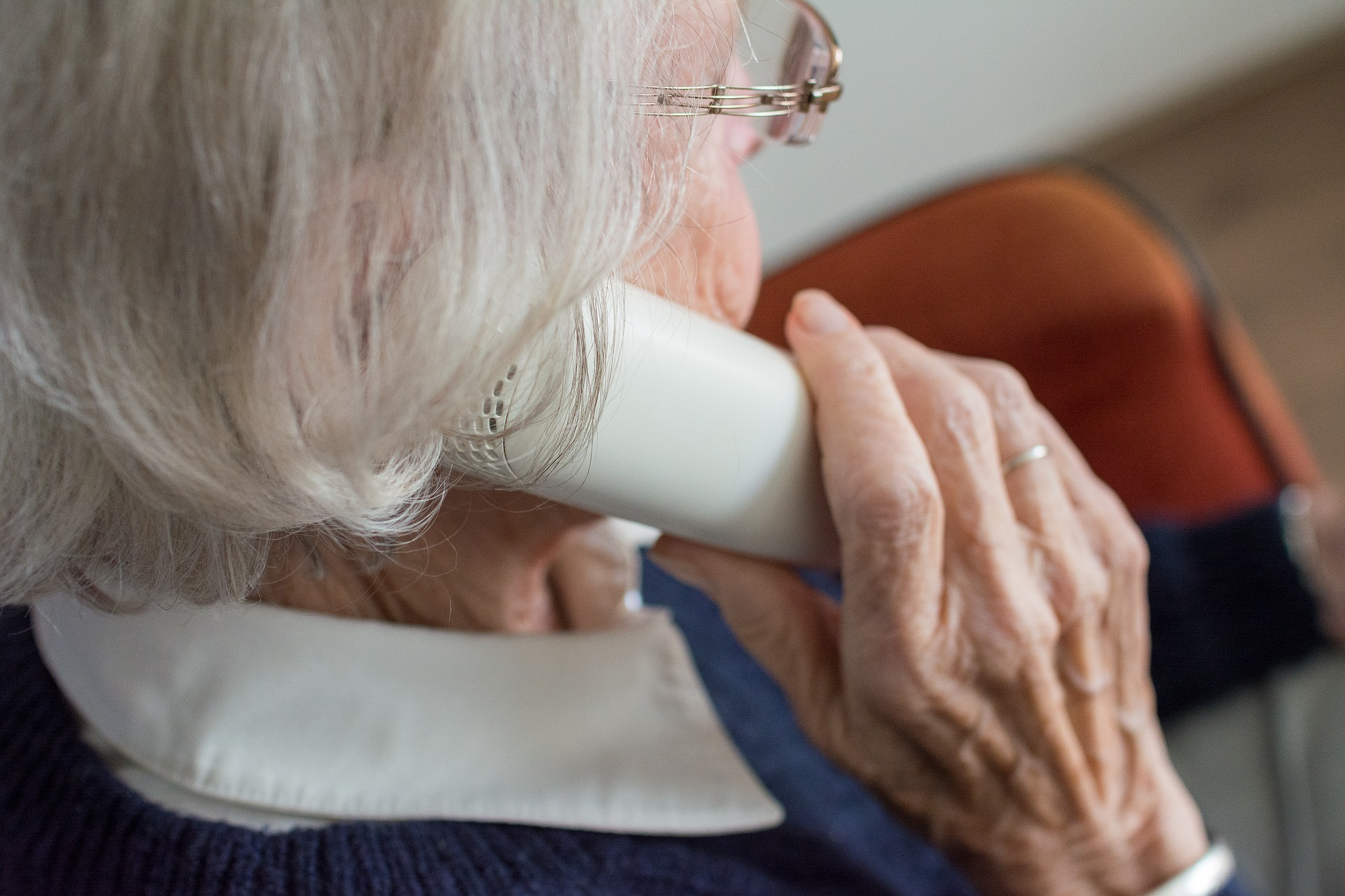 Elderly adult holding telephone to ear