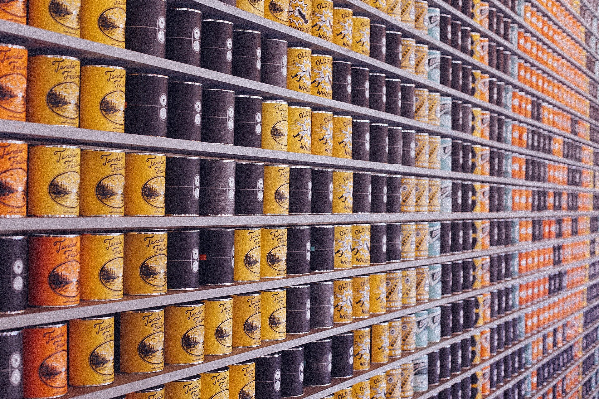 Cans of food stacked on a shelf in a grocery store