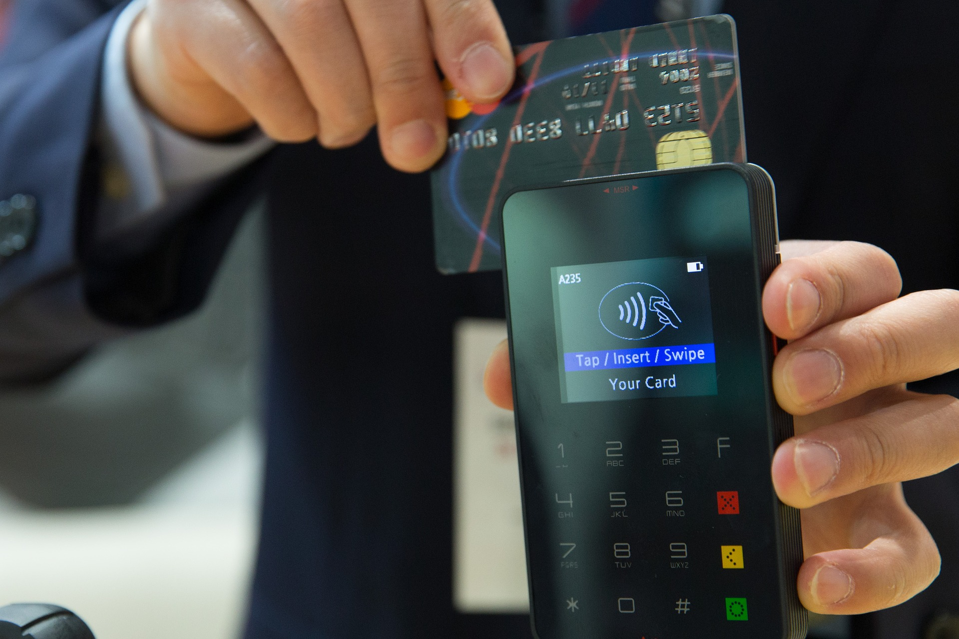 A person swiping a credit card on an eftpos machine