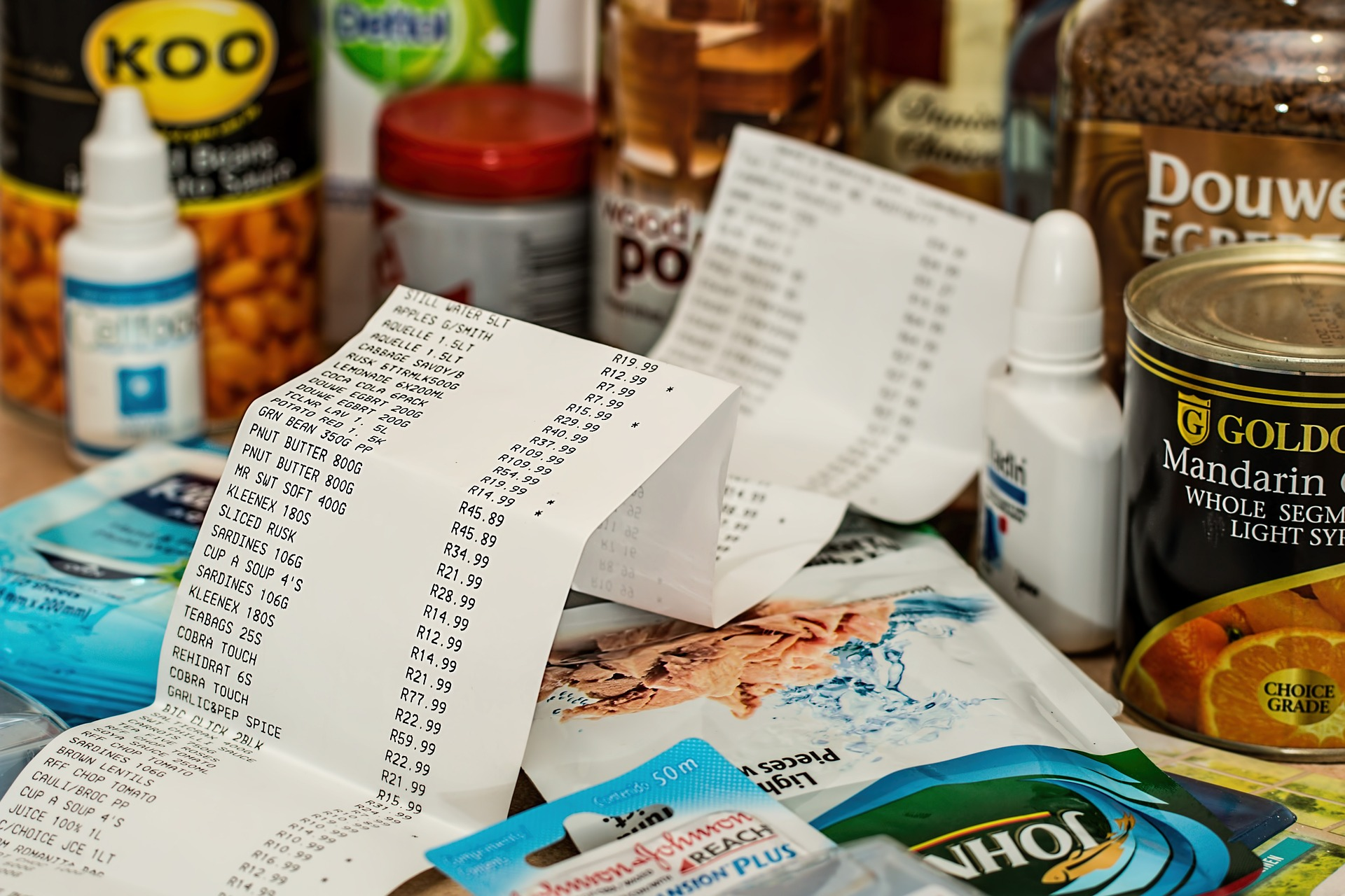 A receipt for grocery items. In the background are grocery items