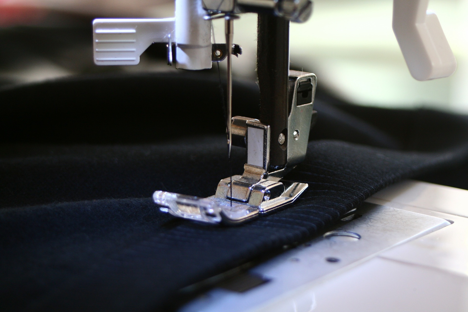 A navy blue piece of fabric being sewn by a sewing machine