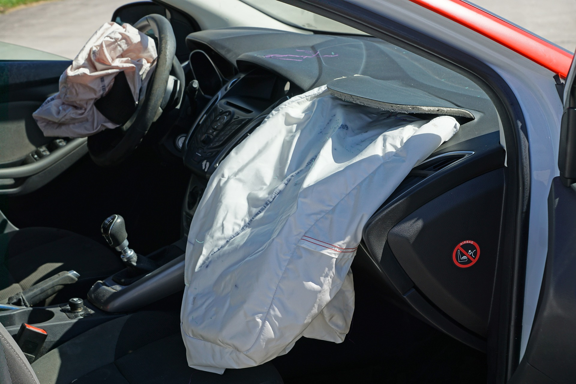 The dashboard of a car; the airbags have deployed and are deflated