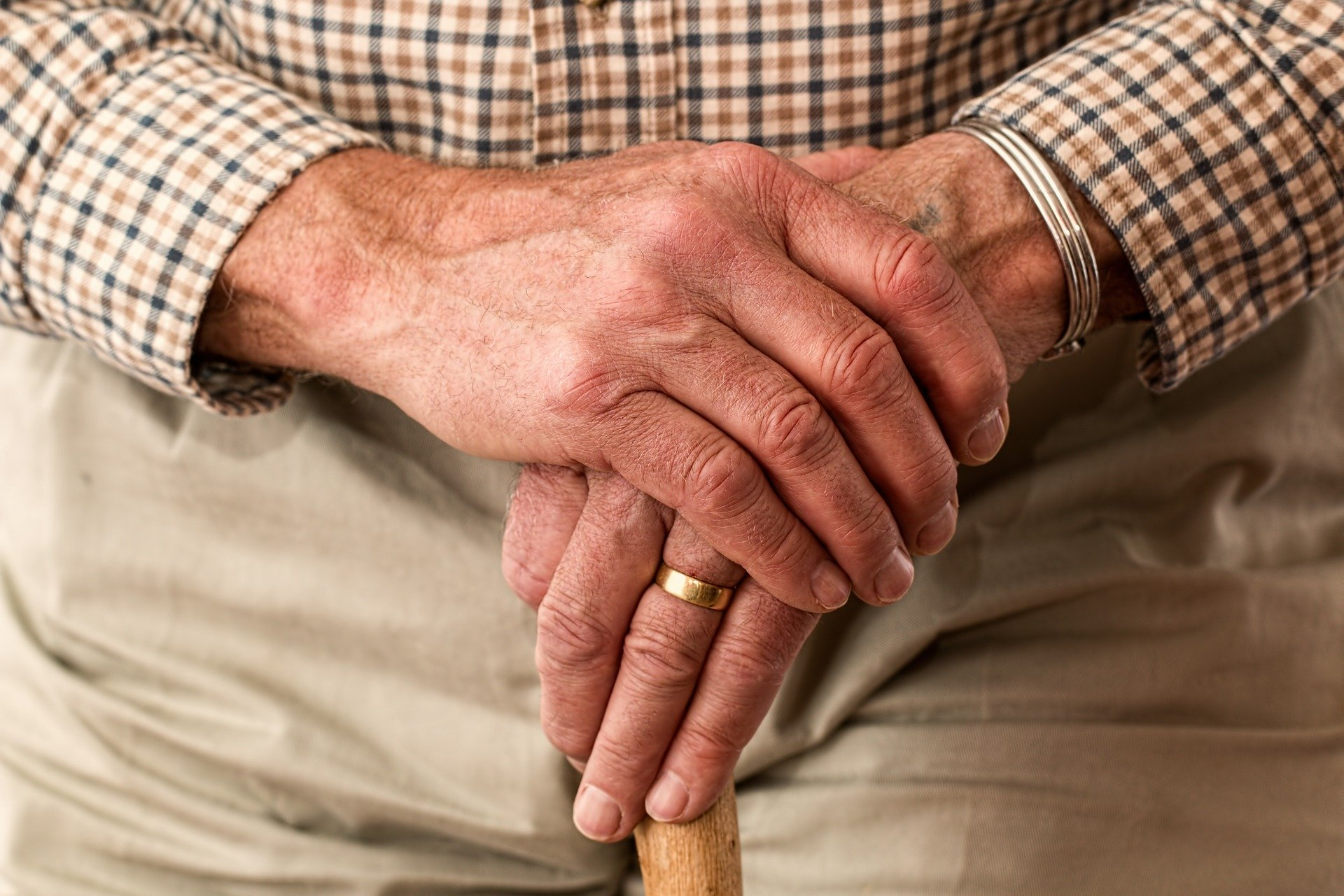 An image of an elderly man's hands holding a walking stick