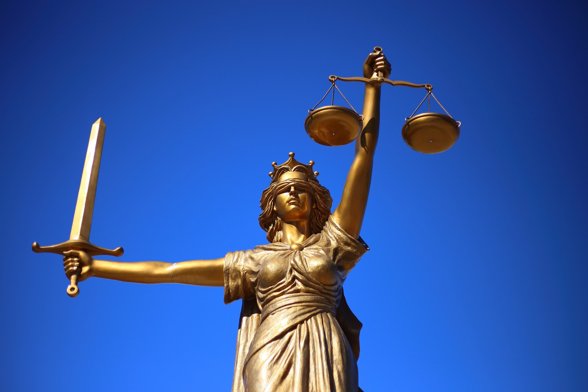 A gold statue of lady justice, a woman holding a sword and scales, in front of a blue background