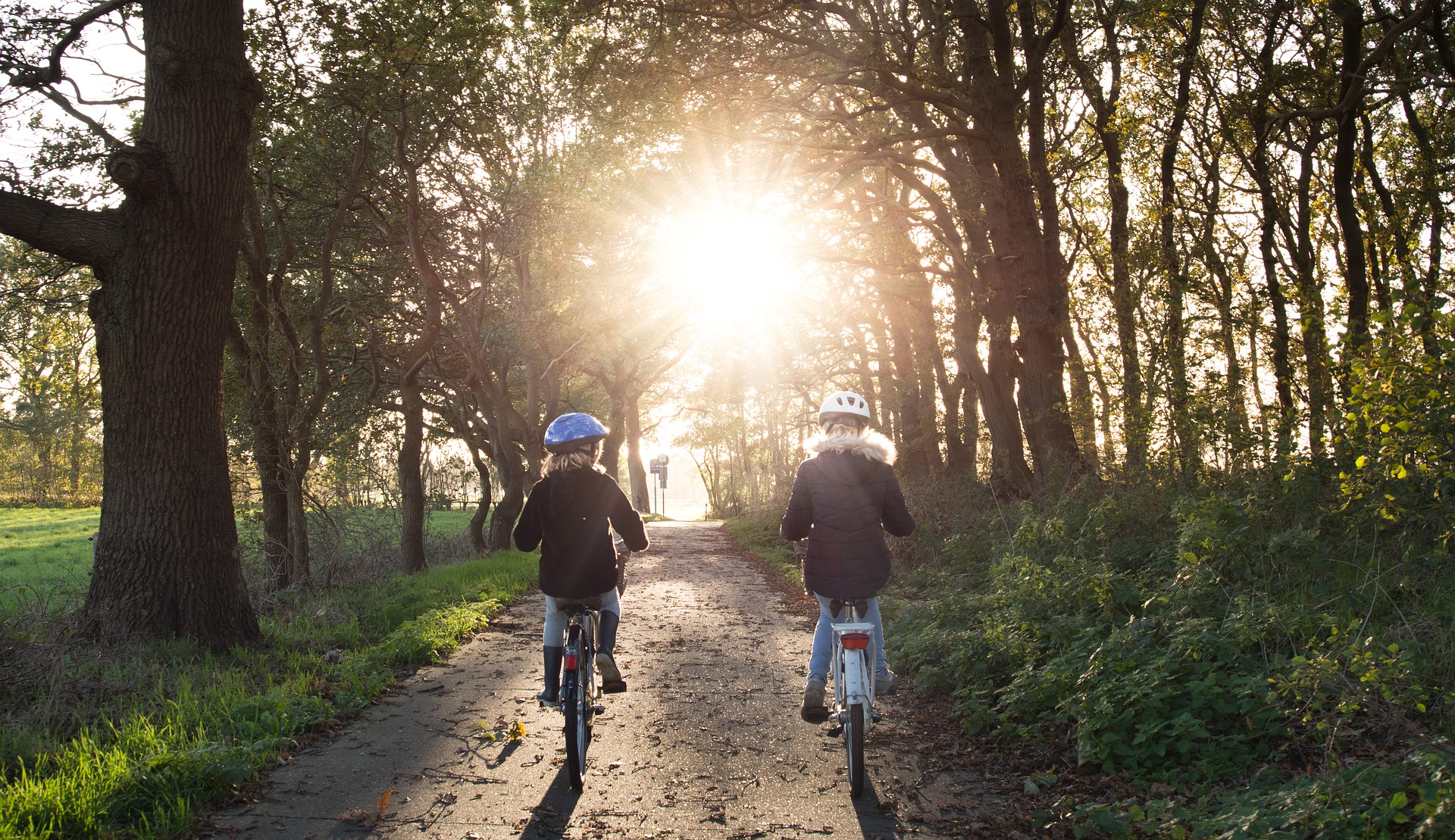 Two children riding bicyles on a path in the woods