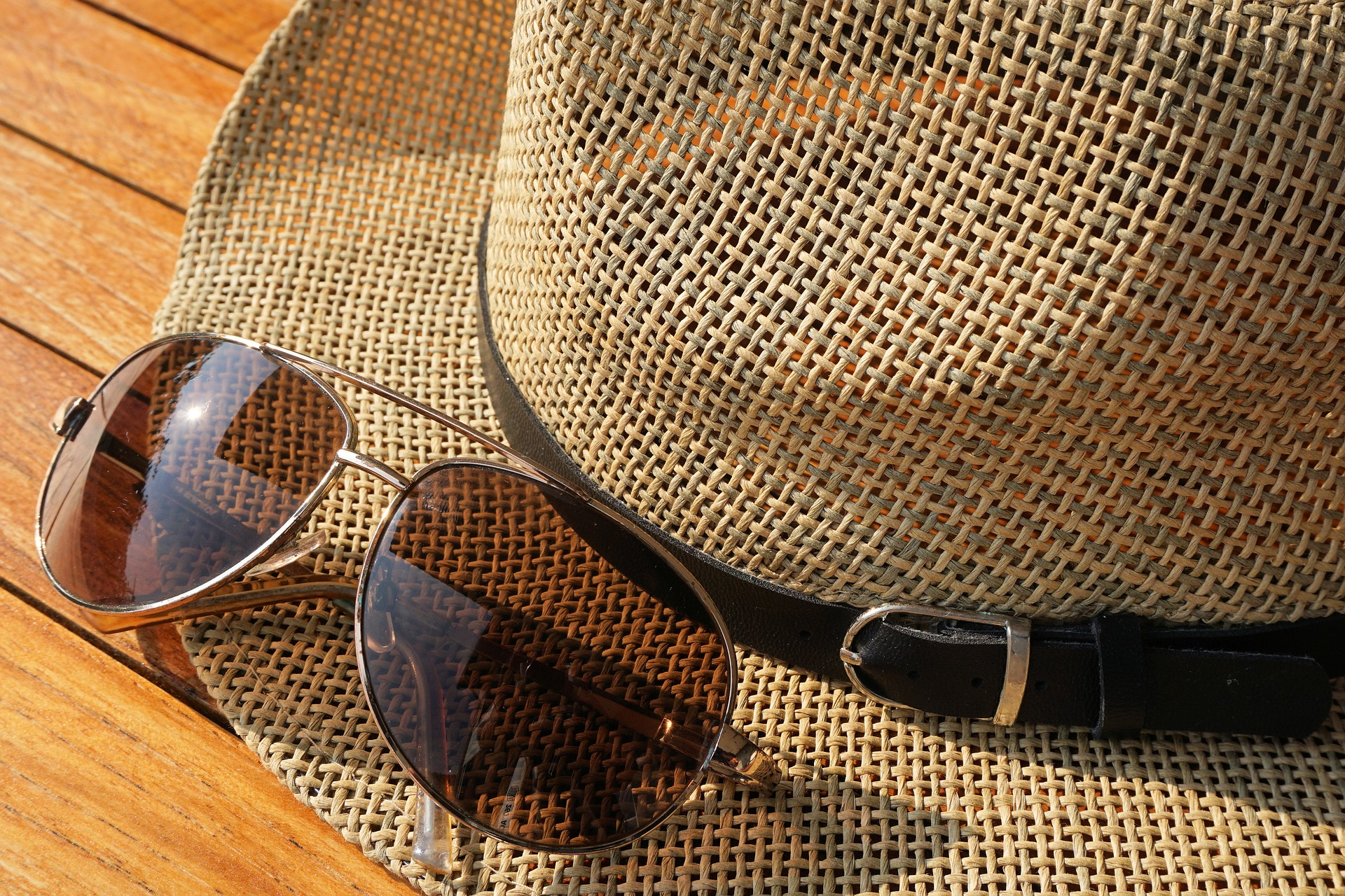 A pair of sunglasses and a woven hat