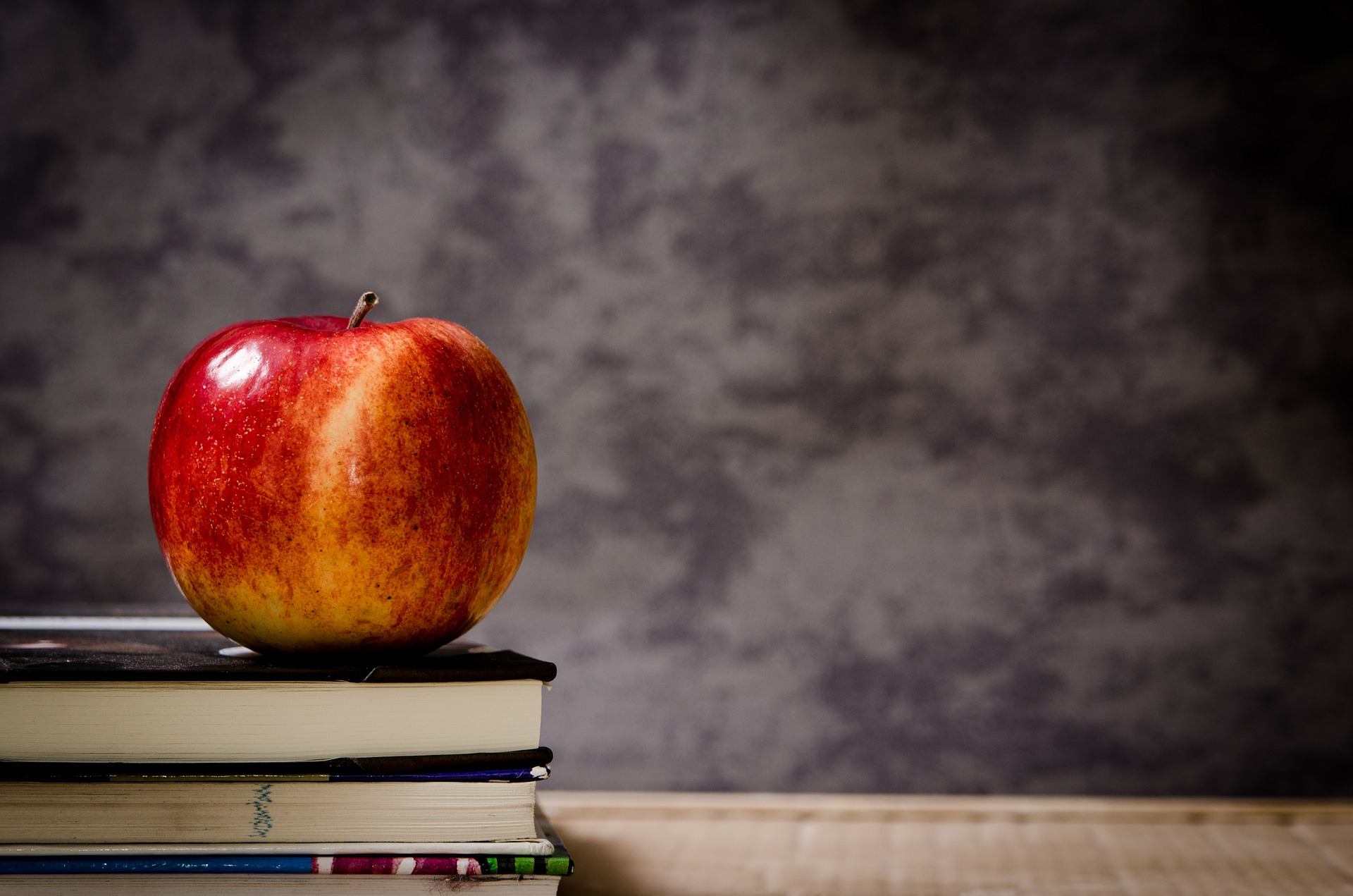 An apple on a pile of school books