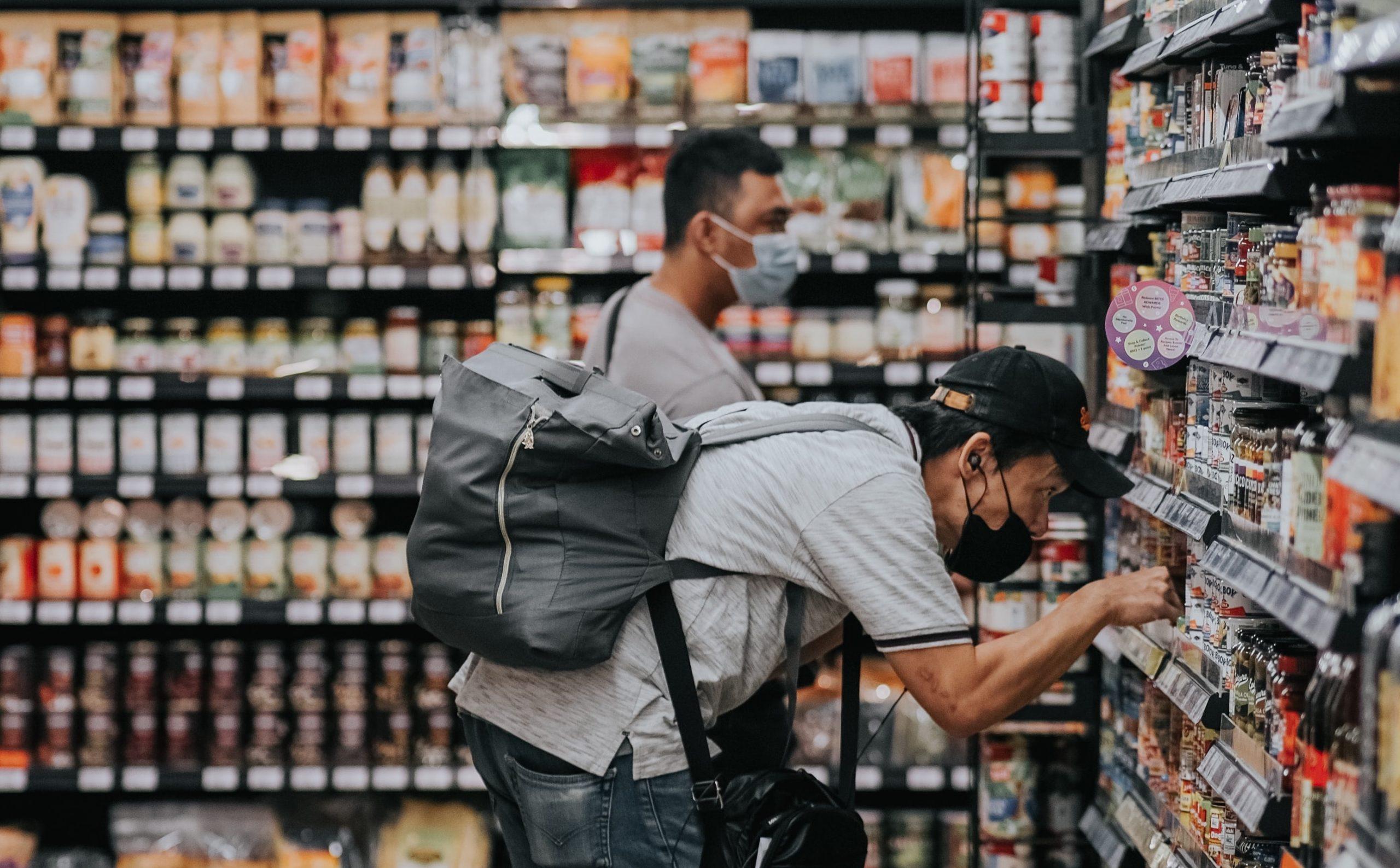 Man in supermarket inspecting shelf