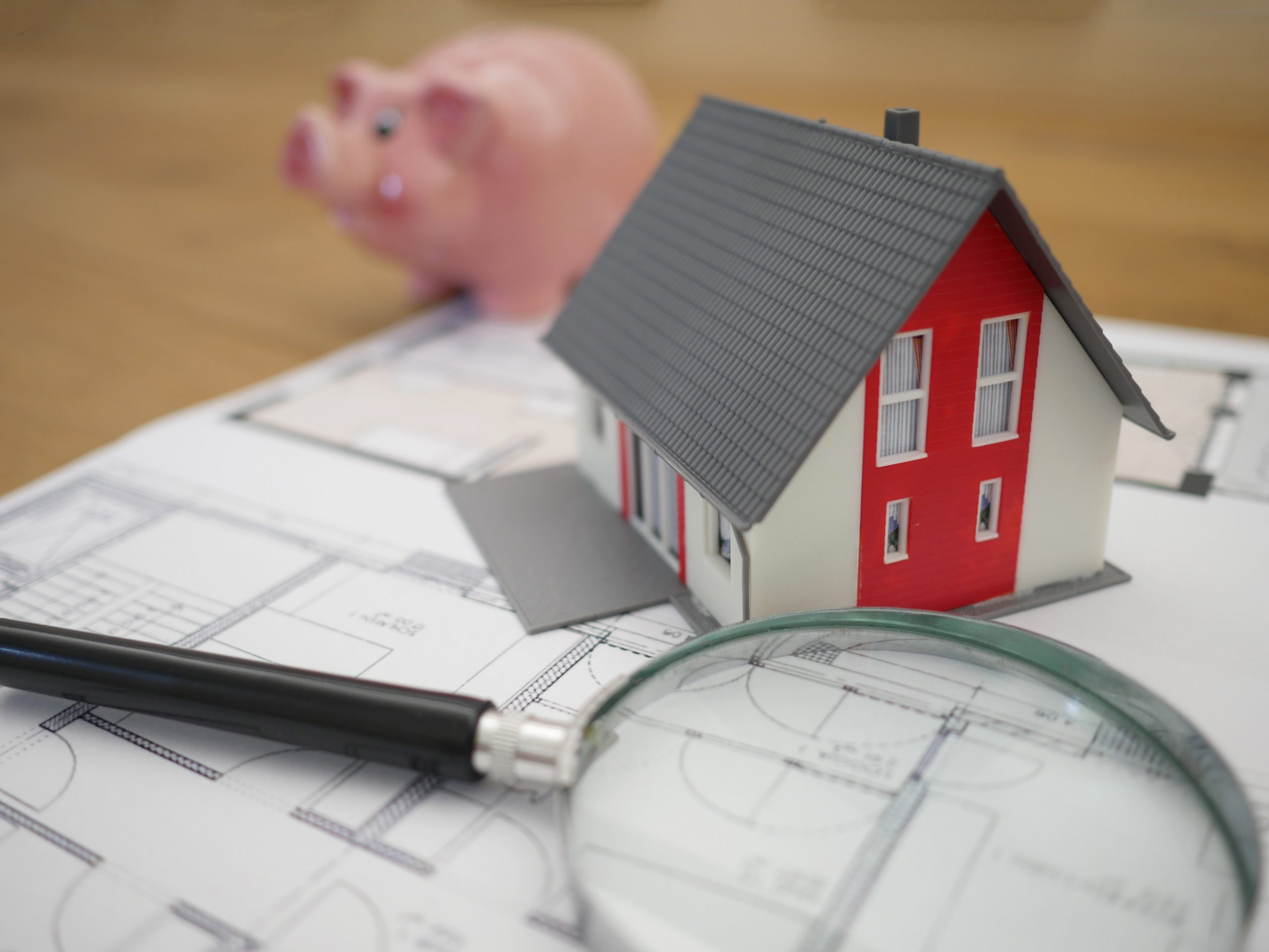 Wooden house, piggy bank, magnifying glass
